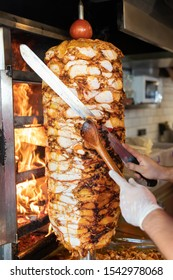 Chef cutting with doner knife Traditional Turkish Doner Kebab meat. Shawarma or gyros. Turkish, greek or middle eastern arab style chicken doner kebab food on isolated white.