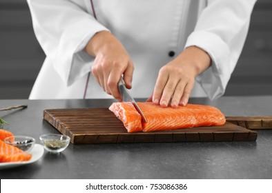 Chef cutting fresh salmon fillet in kitchen