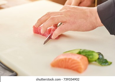 Chef cutting fresh tuna in small pieces. The process of slicing raw tuna fillet by chef. Chef at work, cooking.