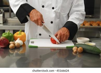 A chef cutting fresh vegetables in a restaurant kitchen.