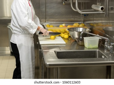Chef cutting lemons in commercial stainless steel kitchen in restaurant
