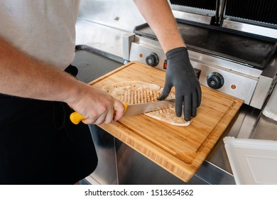 Chef cutting Mexican taco on wooden board to serve it
