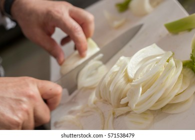Chef cutting onions on white board