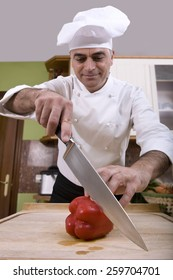 Chef cutting a pepper, with a kitchen knife.