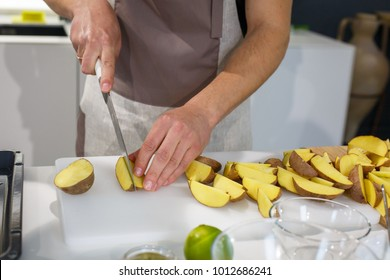 Chef cutting potatoes wedges on white table. Family dinner on holidays. Cooking in cozy cuisine at home