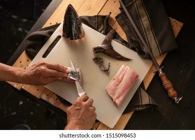 Chef cutting raw fish , close-up. Woman chef cutting raw fish  for dinner dish in the kitchen, close-up.