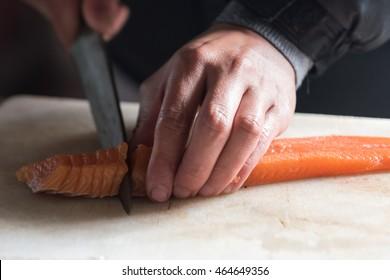 chef cutting salmon for Sashimi.
