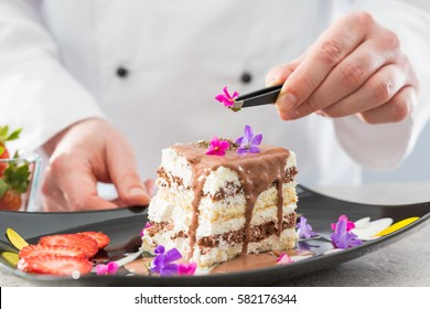 Chef decorate dessert. Decoration of flowers and fruit. Cake with icing.