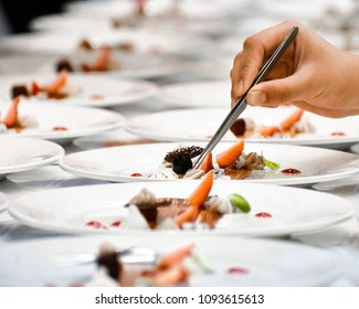 A chef decorates many plates of cake