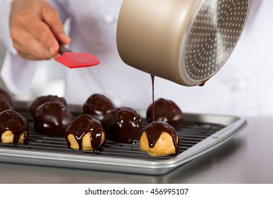 Chef decorating a chocolate profiteroles filled with cream