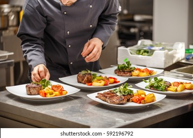Chef is decorating delicious dish on restaurant kitchen board