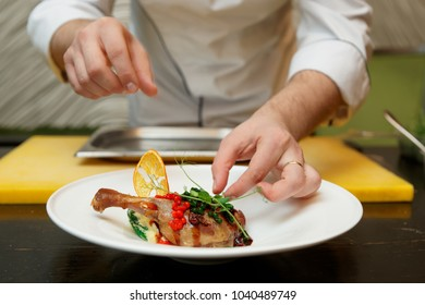 Chef is decorating a dish - fried duck leg with orange chip