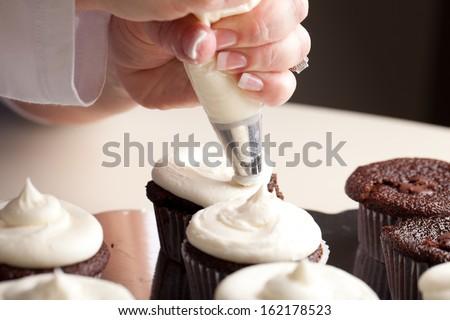 Chef decorating and piping buttercream icing on chocolate filled chocolate cupcakes - bakery