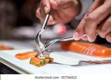 Chef decorating sliced salmon with cream