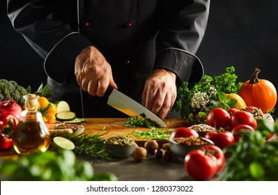 Chef dicing fresh herbs on a wooden chopping board with a kitchen knife while preparing salad in a close up on the hands