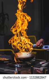Chef doing flambe to food in pan with alcohol in big flame Hotel Service