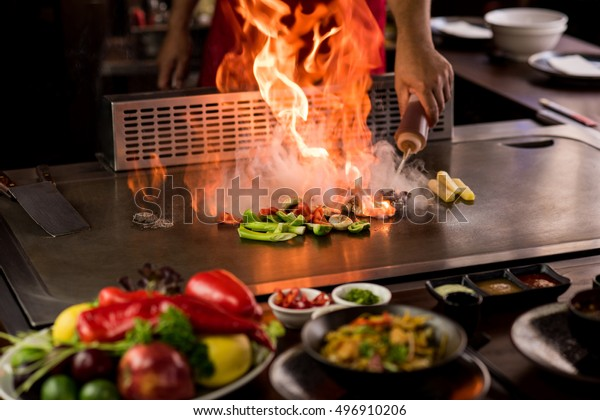 Chef doing flambe while preparing teppanyaki