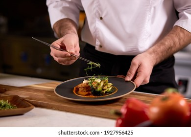 chef dressing salad with fresh greens, adding finishing touch on dish before it is going to be served for restaurant guests