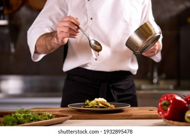 chef dressing salad with sauce, pouring sauce into plate, finishing cooking of meal in restaurant kitchen, cropped man in apron at work