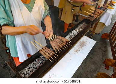 chef during the preparation of street food many skewers with lamb meat cooked grilled