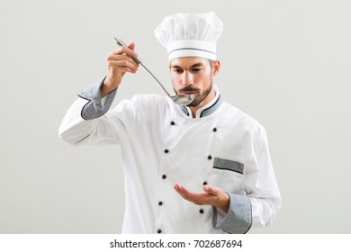 Chef enjoys tasting soup that he has made.Satisfied chef
