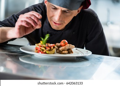 Chef finishing and garnishing food he prepared, a dish with pork meat and vegetables