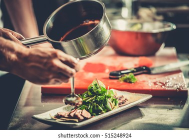 Chef finishing her plate and almost ready to serve at the table. Only hands. Finally dish dressing: steak meat with green salad