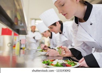 Chef finishing her salad in culinary class in kitchen