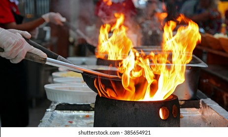 Chef Flambe Cooking. Professional chef in a commercial kitchen cooking flambe style.  Chef frying food in flaming pan on gas hob in outdoor kitchen.