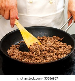 Chef frying minced meat in a pan