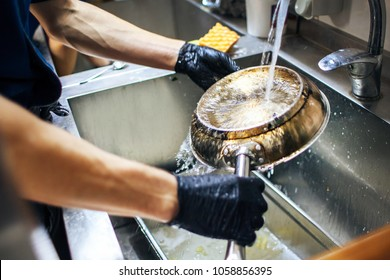 chef in gloves washes the pan under the faucet