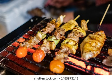 The chef is grilling BBQ, sauce with Sichuan pepper, The young man grilled a barbecue in the gas stove at night. Barbecue grill vendors selling on the way