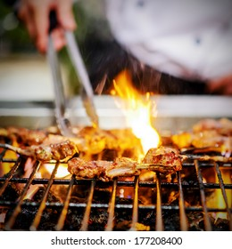 chef grilling lamb ribs on flame