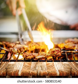 chef grilling lamb ribs on hot flame , barbecue cooking in evening and sunset with wooden table perspective