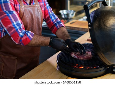 Chef grilling steak in a restaurant