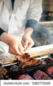 Chef grilling Unagi eel  on char griller for Japanese Unagi donburi (Unadon) rice recipe, famous street food of Narita, Chiba, Japan.