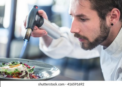 Chef grills goat cheese on vegetable salad with kitchen mini blow torch.