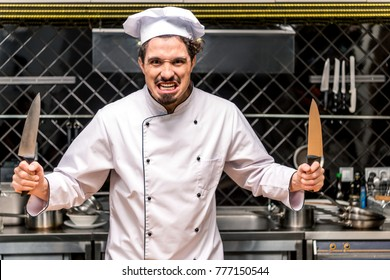 chef grimacing and holding two knifes in hands