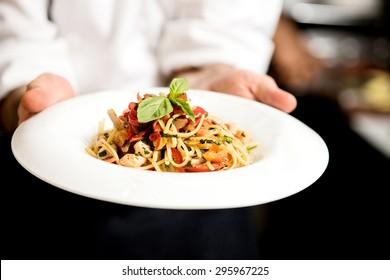 Chef hand holding tasty pasta dish