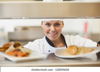 Chef handing dinner plates through order station in the kitchen