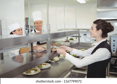 Chef handing food dish to waitress at order station in the commercial kitchen