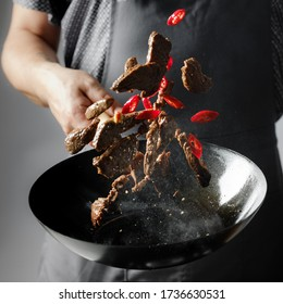 Chef hands cooking beef meat slice in wok pan with salt and chilli pepper. Professional restaurant and hotel service food concept.
