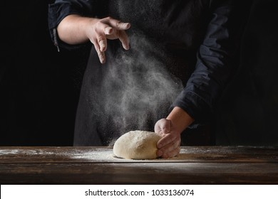 Chef hands cooking dough on dark wooden background. Food concept.