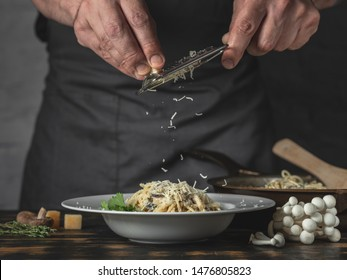 Chef hands cooking Italian pasta and adding cheese parmesan in dish on wooden table background.