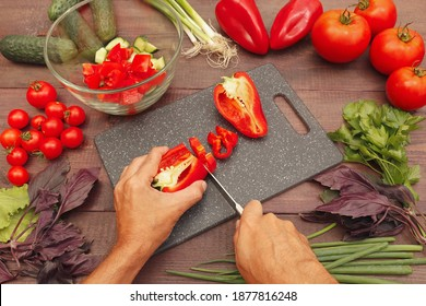 Chef hands cut fresh bellpepper on a rustic wooden table.