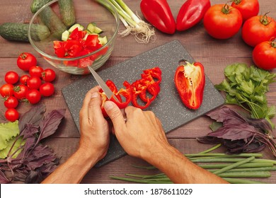 Chef hands cut fresh bellpepper for salad on a wooden table.