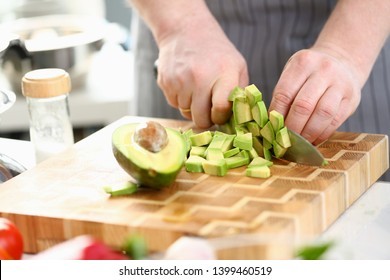 Chef Hands Cutting Dieting Tropical Fruit Avocado. Man Chopping Exotic Ingredient with Sharp Knife on Wooden Cutting Board. Male Cooking Organic Dish in Kitchen. Home Culinary Horizontal Photography