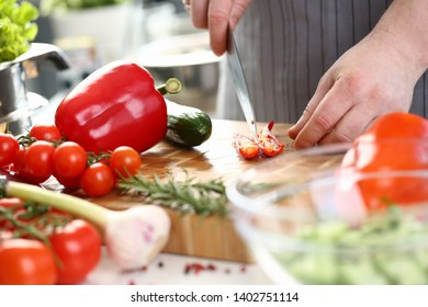 Chef Hands Cutting Red Hot Chili Pepper Halves. Assorted Vegetables on Wooden Board. Male Cooking Dieting Salad. Natural Vegetarian Aromatic Ingredient. recipe of Delicious Dish Horizontal Photo