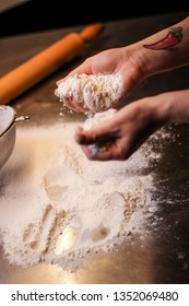 The chef hands mixes the dough from flour and eggs. Smoke flour. Kitchen processes.
