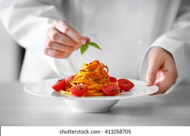 Chef hands preparing delicious cold pasta salad on the table closeup